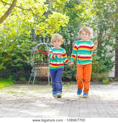Two little sibling kid boys in colorful clothing walking hand in