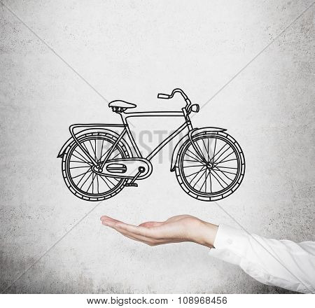 A Hand In Formal White Shirt Holds A Model Of A Sketched Bicycle. Concrete Wall On Background. A Con