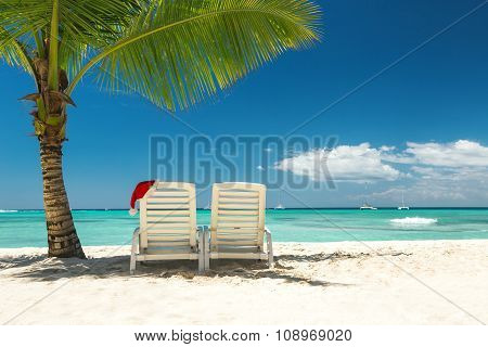 Santa's Hat And Sun Loungers On The Tropical Beach
