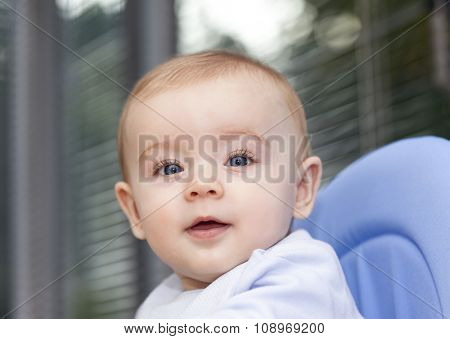 Baby sitting on a chair looking to the camera