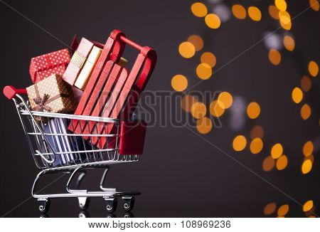 Shooping cart with red sled full of gift boxes on dark background