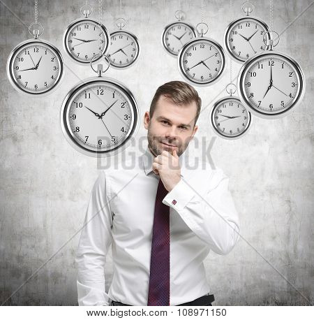 A Thinking Handsome Businessman Is Holding His Own Chin. Several Models Of Pocket Watches Are Hoveri