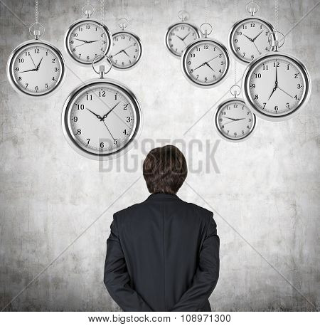 A Rear View Of A Businessman Who Is Looking At The Hovering Pocket Watches In The Air. A Concept Of