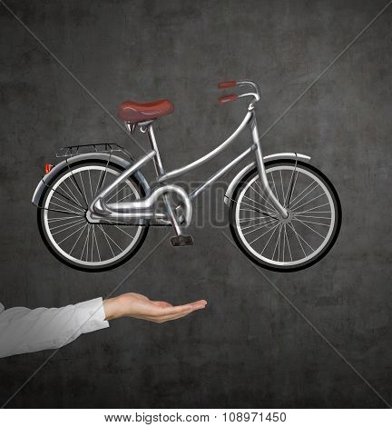 A Hand In Formal Shirt Holds A Bicycle Which Is Drawn On The Black Chalkboard Wall. A Concept Of Tra