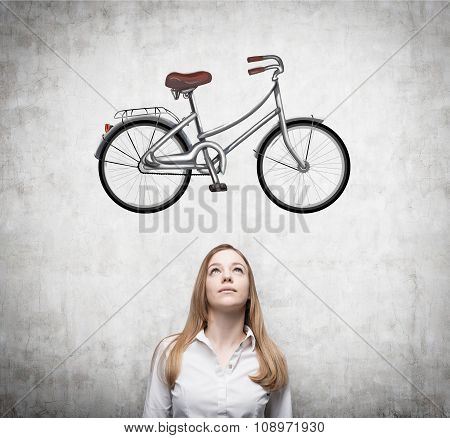 A Beautiful Girl In Formal Clothes Is Dreaming About A New Bicycle. A Sketch Of A Bicycle Is Drawn O