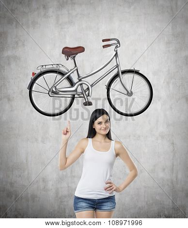 A Brunette Girl In A White Tank Top And Denim Shorts Points Out The Bicycle By Her Finger. A Sketch