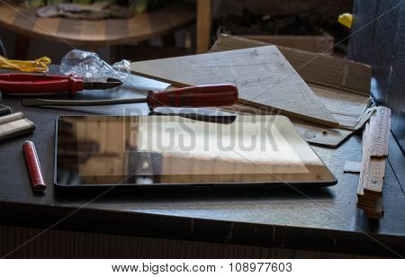 Tablet With Reflection On A Dark Cupboard With Tools