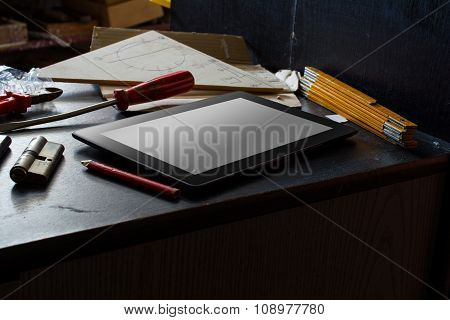 Tablet With Blank Screen On A Dark Cupboard With Tools In A Dirty Basement