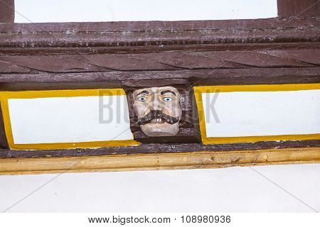 Wood Carving With Funny Faces On Timber Balk  Of Old Framework Houses