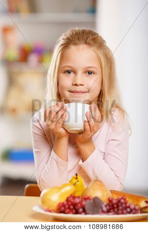 Little girl is drinking tea.