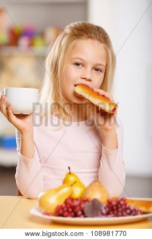 Little girl is drinking tea and eating pastry.