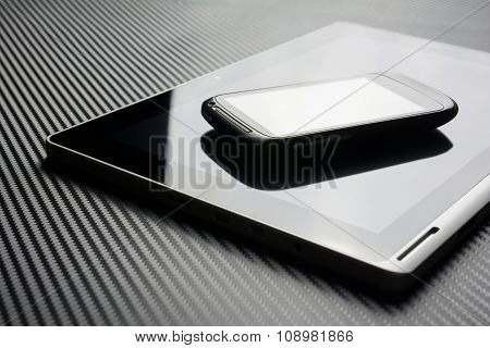 Blank Smartphone With Reflection Lying On Business Tablet With Reflection On Carbon Background