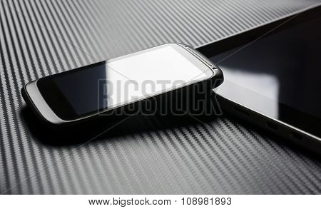 Blank Business Smartphone With Reflection Leaning On Tablet With Carbon Background