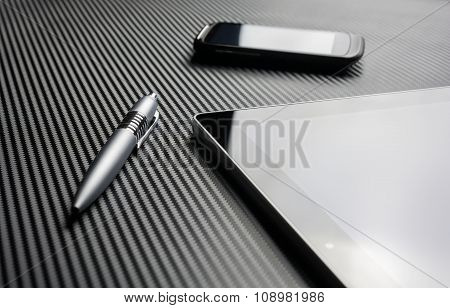Blank Smartphone With Reflection And A Pen Lying Next To A Business Tablet On A Carbon Layer