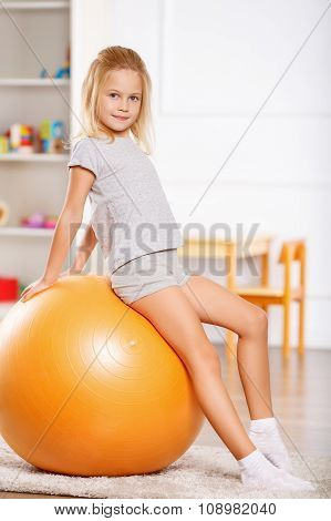 Little girl leaning against a gym ball.