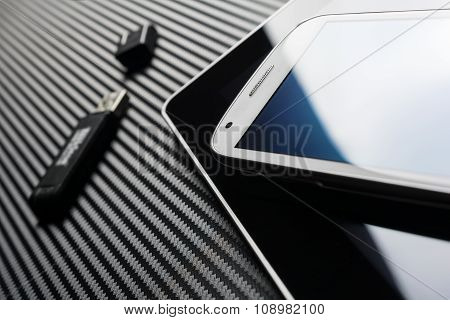 Business Smartphone With Blue Reflection Lying On Blank Tablet Next To An USB Storage Above Carbon