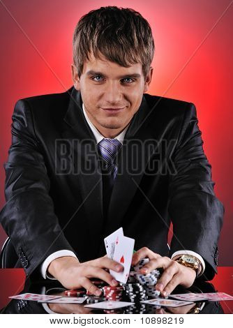 Handsome poker player with two aces in his hands