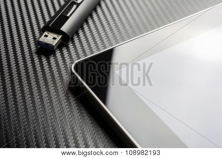 Usb Storage Flash Drive Lying Next To Blank Business Tablet With Reflection On Carbon Background