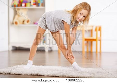 Little girl doing exercises at home.