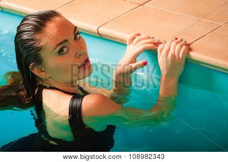 Portrait Of Woman Relaxing In Water At Poolside