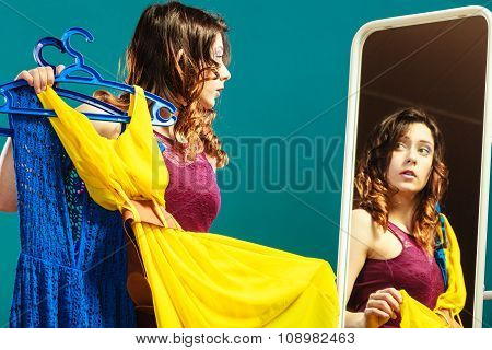 Woman Shopper Holds Hangers With Clothes Looking In Mirror