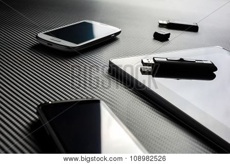 2 Business Mobiles With Reflections And An USB Drive Lying Next To A Blank Tablet With An USB Drive
