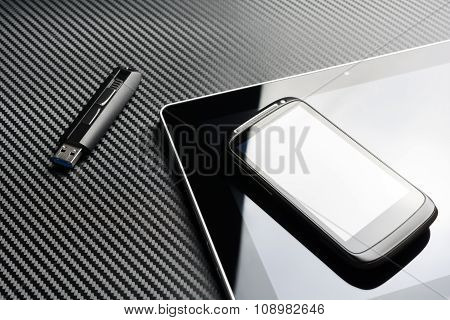 Blank Smartphone With Reflection Lying On Business Tablet Next To An USB Drive Above A Carbon Layer