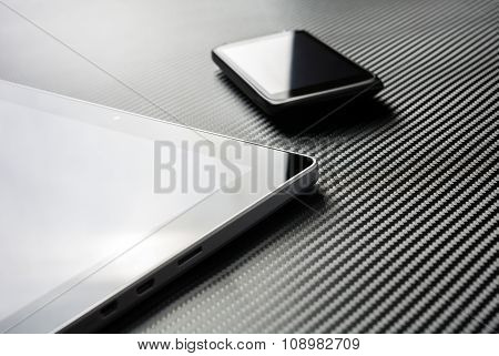 Business Mobile With Reflection Lying Next To Blank Tablet On A Carbon Layer