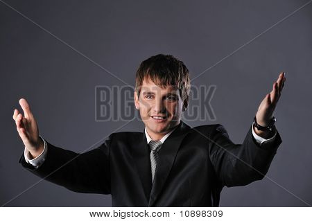 Happy young businessman with an open hands