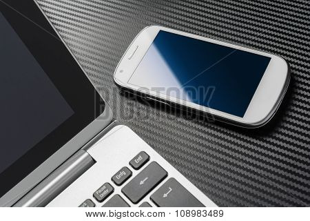 White Business Smartphone With Blue Reflection Lying Right To A Notebook, All Above A Carbon Layer