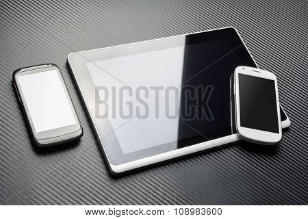 Black Mobile Lying Next To A Business Tablet With Reflection And A White Phone On Carbon Layer