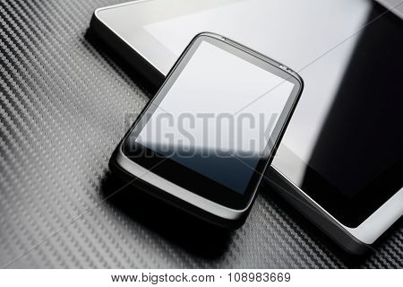 Blank Black Business Smartphone With Blue Reflection Leaning On A Notebook Keyboard Next To A Plugge