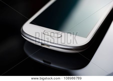 A White Smartphone On A Tablet