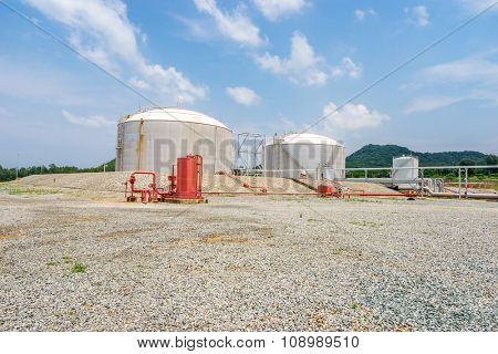 oil tanks stand in empty ground in blue sky