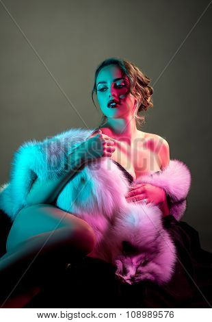 Erotica. Sensual nude model in luxurious fur coat