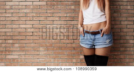Half Body Shot Of A Cheerful Stylish Woman In Denim Shorts And White T-shirt, Against Brick Wall Bac