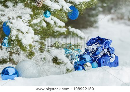 Live snowy pine tree decorated with Christmas ornaments and wrapped presents beneath it