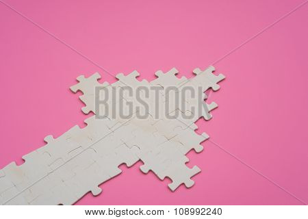 Jigsaw Puzzle Shaped Like An Arrow Going Up On Pink Background