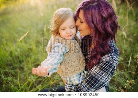 Mother And Daughter Sitting On The Field In Sunset