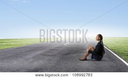 Bored young businesswoman sitting alone on asphalt road