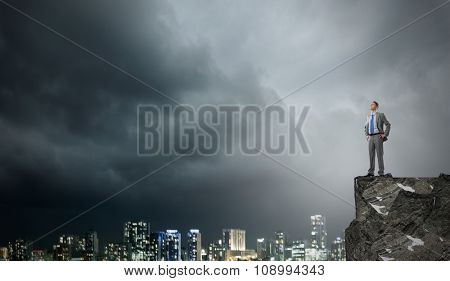 Young confident businessman standing on rock top