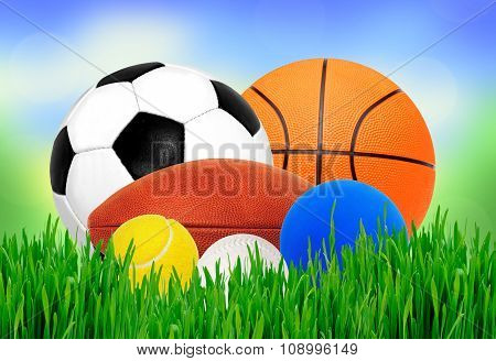 Sport Balls In Green Grass Over Blurred Nature Background