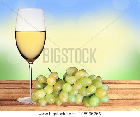 Glass Of White Wine And Green Grape On Wooden Table Over Nature Background