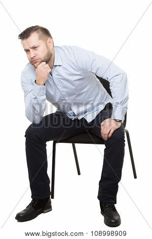 man sitting on chair. Isolated white background. makes decisions. aggressive. hand under chin