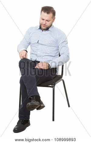 man sitting on chair. Isolated white background. removes dust particles, looking down