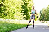 Постер, плакат: fitness sport summer rollerblading and healthy lifestyle concept happy young woman in rollerbla