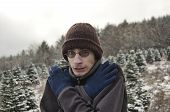 picture of shivering  - Young man shivers rubbing his hands together in the snow - JPG