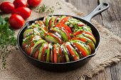 Постер, плакат: Raw vegetable ratatouille in cast iron frying pan preparation recipe on vintage wooden table backgro