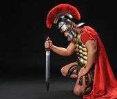 stock photo of spartan  - Portrait of a legionary soldier standing on his knee - JPG