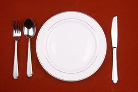 foto of christmas dinner  - place setting of a dinning set in red background - JPG